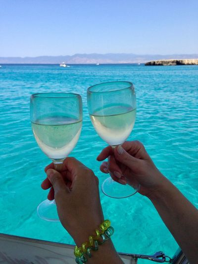 Sommergefühle Summer Colors Sea Real People Water Holding Food And Drink Day Outdoors Human Hand Lifestyles Leisure Activity Horizon Over Water Sky Blue Human Body Part Drinking Glass Clear Sky Nature Women Men Drink
