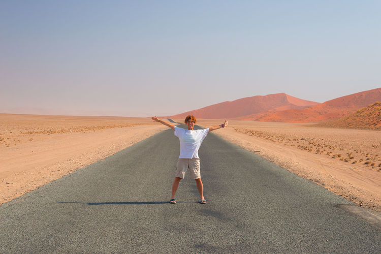 View of woman standing in desert against clear sky