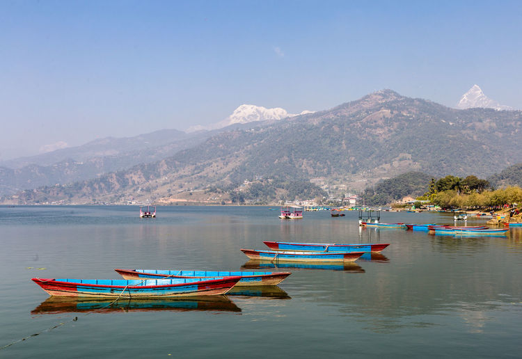 Boats moored in sea against mountains