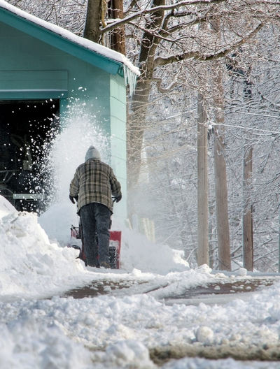 Rear view of man removing snow by house during winter