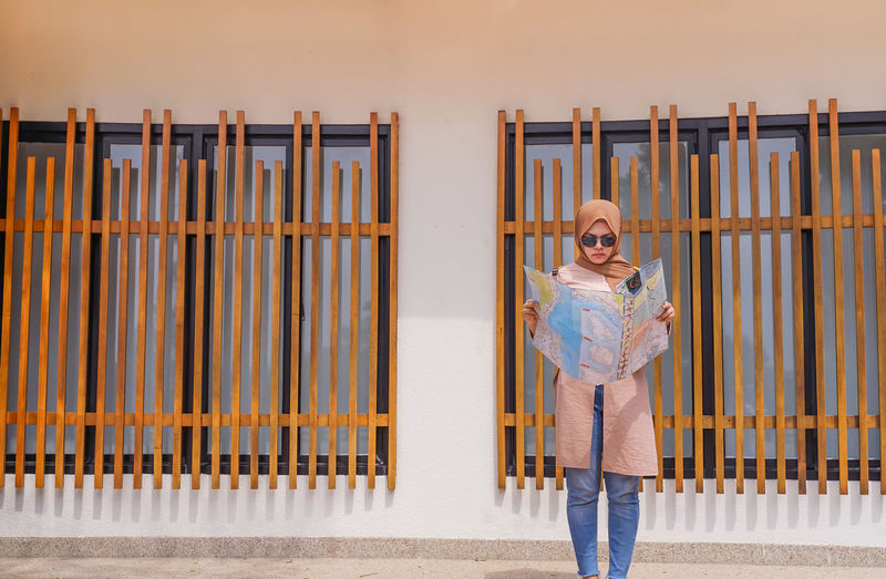 Portrait of girl standing against railing