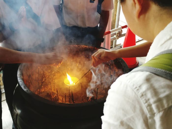 People Igniting Incense From Flame At Temple