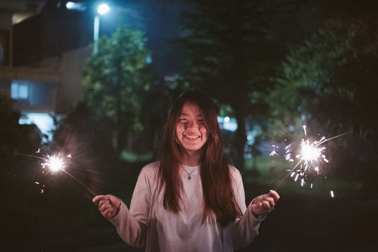 Portrait of smiling young woman with firework display at night