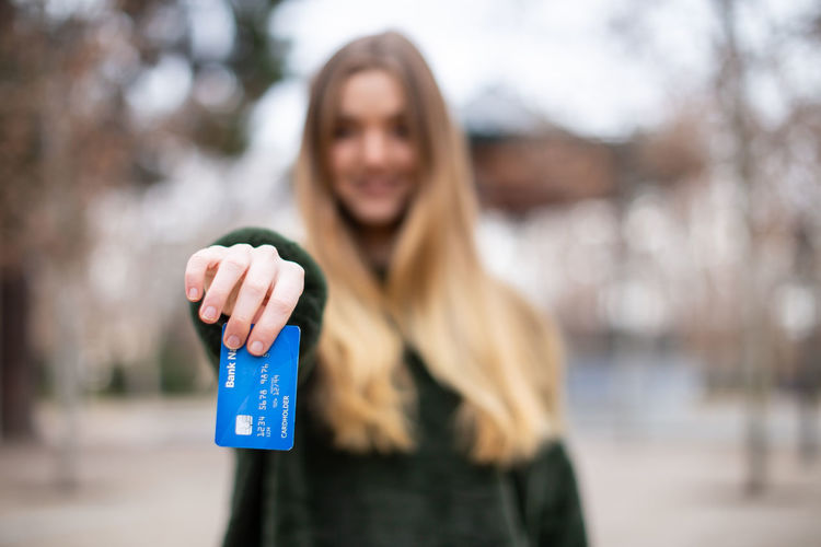 Happy young lady with credit card standing in park Woman Young Beautiful Blonde Happy Beauty person Smile People Phone Smiling Autumn Park Cheerful Outdoors Hair Mobile Face Cute White Holding One Person Happiness Nature Model Credit Credit Card Banknote Choice Showing Buyer Currency Cash Pay Finance Money Investment Transaction Plastic Female Alternative Sales Consumerism Demonstrating Modern Teen