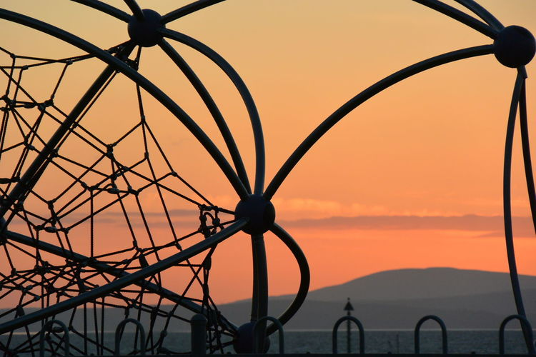 Silhouette of wrought iron fence against orange sky
