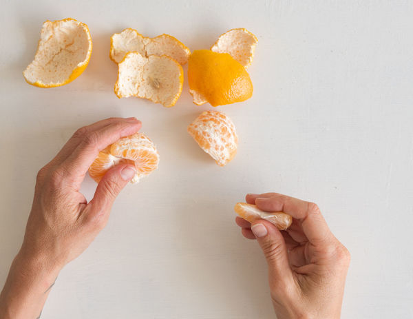 Hands holding orange mandarine segments Body Part Dieting Finger Food Food And Drink Freshness Hand Healthy Eating Holding Human Body Part Human Hand Indoors  Lifestyles One Person Orange Personal Perspective Preparation  Preparing Food Real People Snack Studio Shot Table Wellbeing