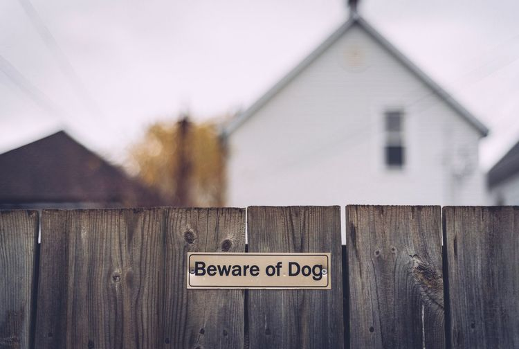 Close-Up Of Beware Of Dog Sign On Fence