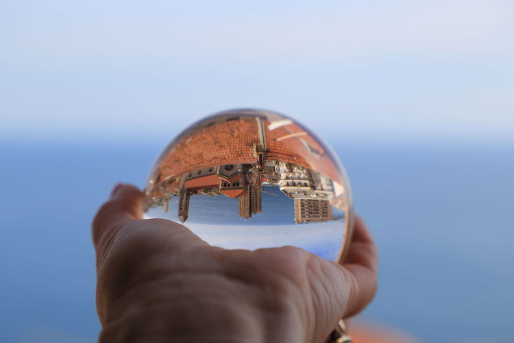 Cropped image of person holding glass ball with upside down reflection of town