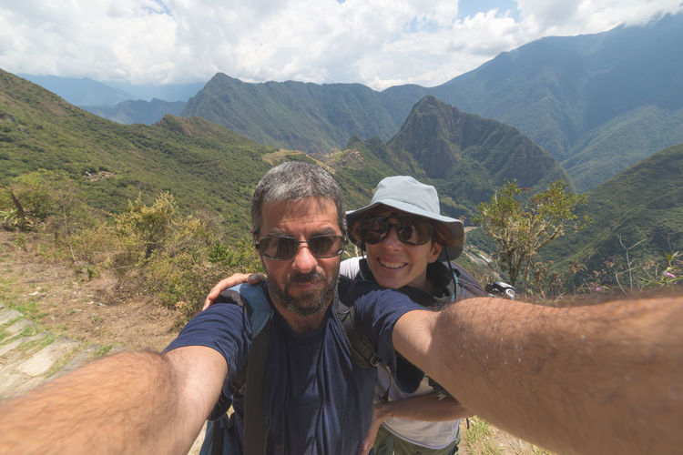 Man and woman taking selfie against mountain