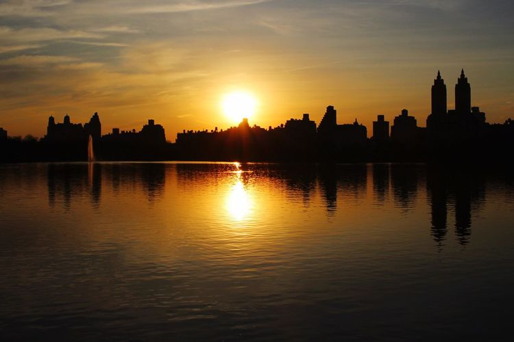 Reflection Of Silhouette Buildings On Lake At Central Park