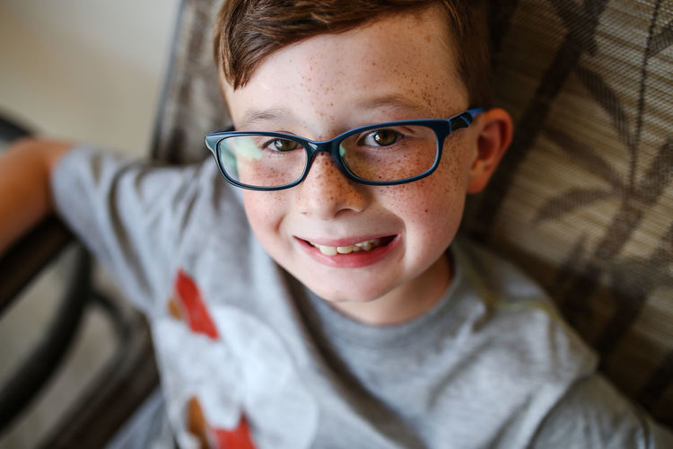 High Angle Portrait Of Smiling Boy Wearing Eyeglasses At Home