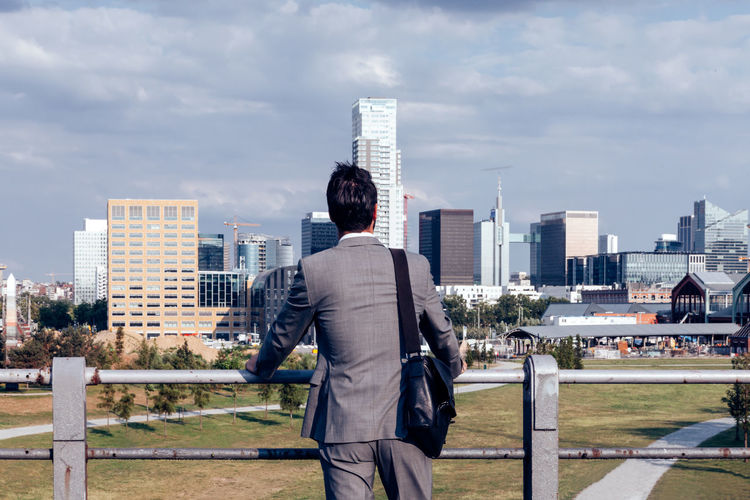 Back view businessman looks from a distance at the financial district of the city - decisions time