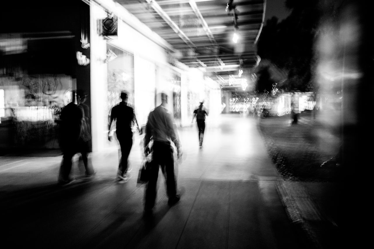 blurred motion, walking, real people, large group of people, built structure, motion, architecture, speed, men, illuminated, transportation, women, night, lifestyles, city, indoors, people