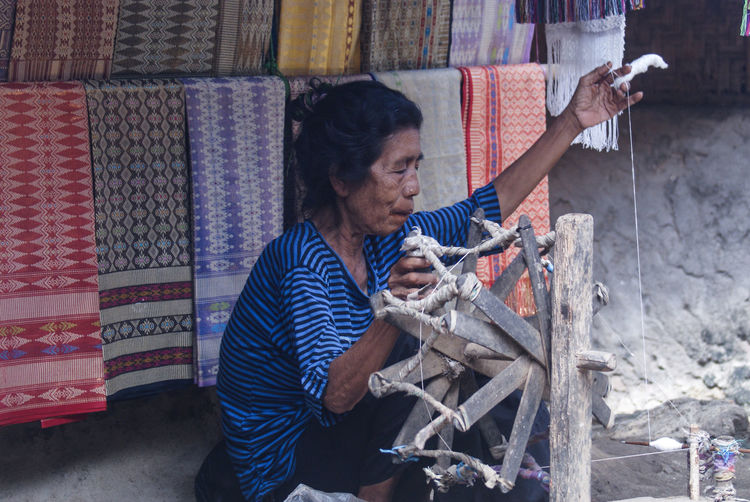 Woman working with thread outdoors