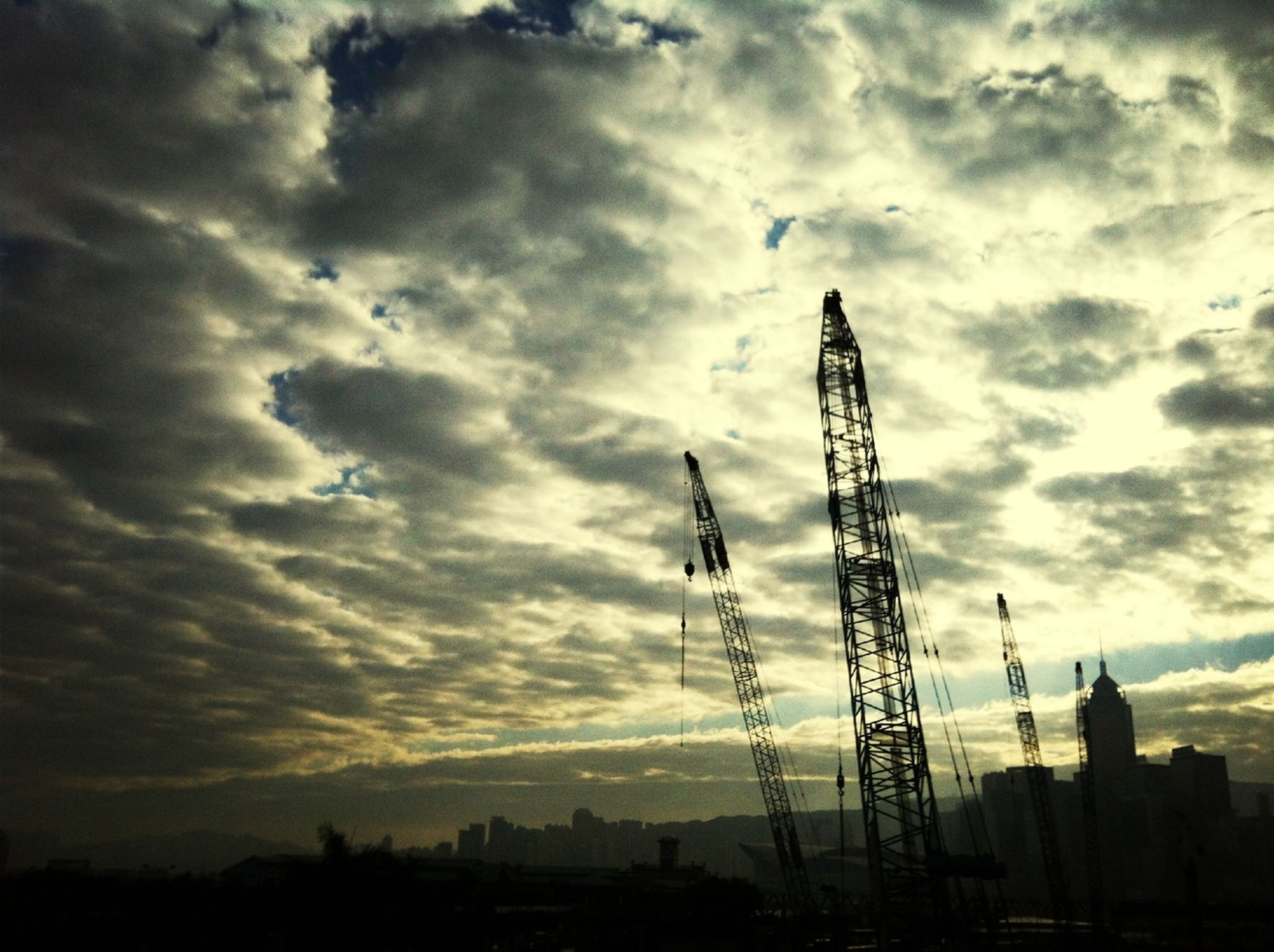 silhouette, sky, sunset, built structure, building exterior, architecture, cloud - sky, low angle view, city, cloudy, cloud, crane - construction machinery, dusk, outdoors, crane, no people, construction site, nature, tall - high, connection