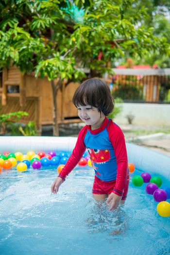 Cute boy playing with ball in swimming pool
