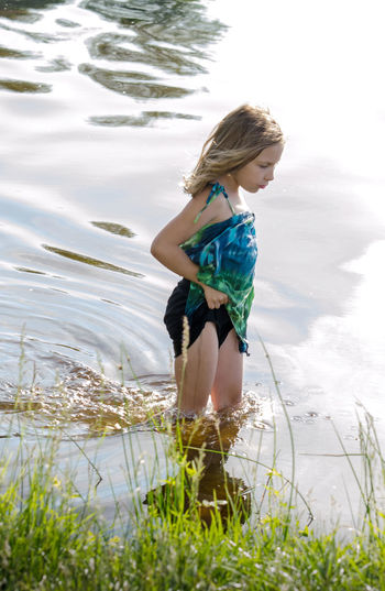 Full length of girl standing by lake against sky