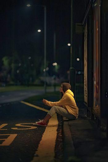 Woman sitting on street at night