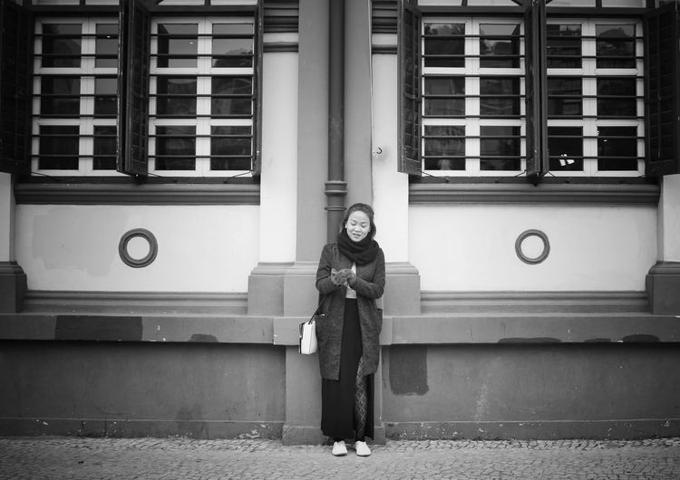 Young woman standing against building