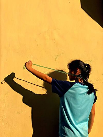 Shadow of girl with skipping rope on yellow wall