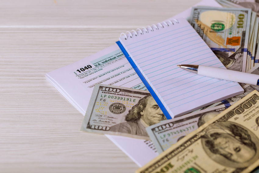 The tax forms 1040 with the money and the pen. IRS Balance Business Close-up Currency Dollars, Money Dollars💲 Economy Federal Finance High Angle View Income Tax Income Tax Return Paper Paper Currency Paperwork Payment Pen Representation Still Life Table Tax 1040 Tax Return Taxation Text