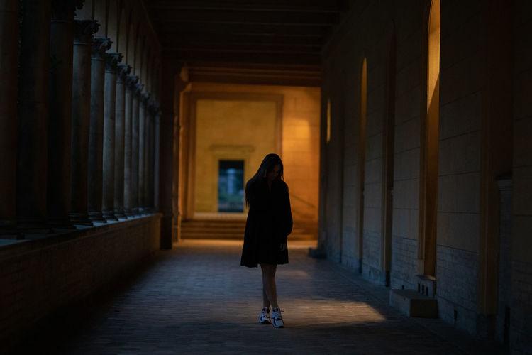 Full length of young woman standing in dark corridor