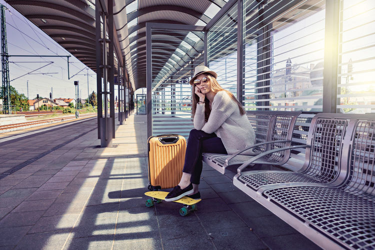 Portrait Of Smiling Young Woman Sitting On Bench At Railroad Station