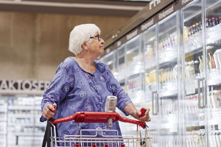 Full length of woman looking away at store