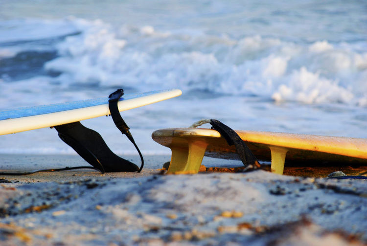 Close-Up Of Surfboards On Sandy Beach