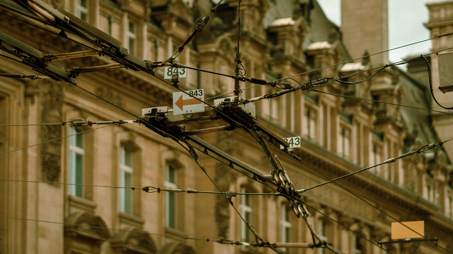 Low angle view of power lines against buildings