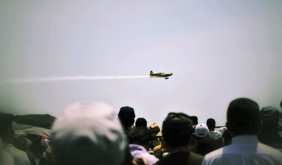 Rear View Of People Looking At Airshow Against Sky