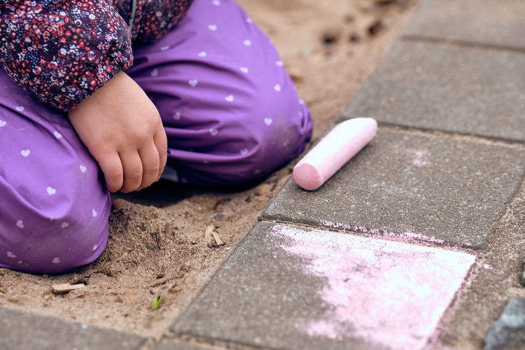 A young girl of about three year painting on the concrete floor of a playground with some children's street chalk. Seen in Nuremberg, Germany, in March 2019 Human Body Part Real People Childhood Child One Person Day Females Selective Focus Baby Sitting Pink Color City Footpath Outdoors Street Young Offspring Lifestyles Purple Innocence Street Chalk Painting Drawing Creativity Creation Creating Learning Concrete Ground Flooring Hands Finger Warm Clothing Season  Winter Springtime White Sand Playground Horizontal Girl Caucasian Daylight Bakgrounds Stone Rock - Object Kindergarten Family Leisure Activity Fingernail