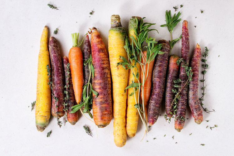 Heap of colorful raw carrots with fresh thyme herbs over white stone surface. Top view. Herbs Assortment Carrot Carrots Colorful Vegetables Colorful Veggies Directly Above Food Food And Drink Freshness Group Of Objects Healthy Eating Healthy Food Multi Colored Raw Food Raw Vegetables Root Vegetable Top View Uncooked Variety Vegetable White Background Yellow Carrots