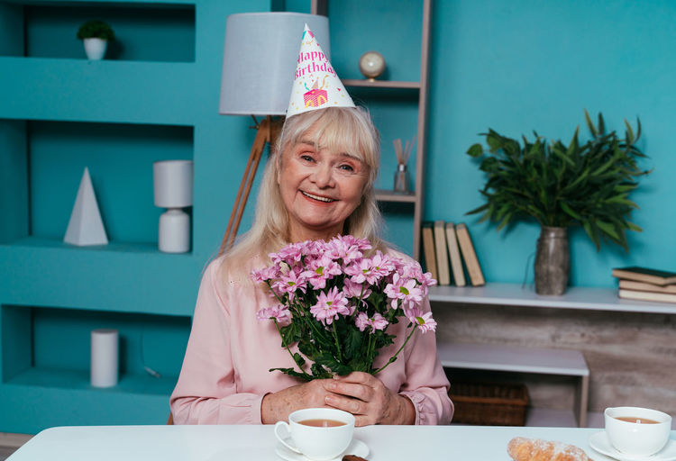 Portrait of smiling senior woman holding flowers at home