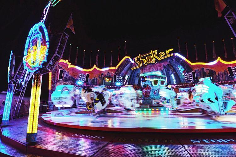 Illuminated carousel in amusement park at night