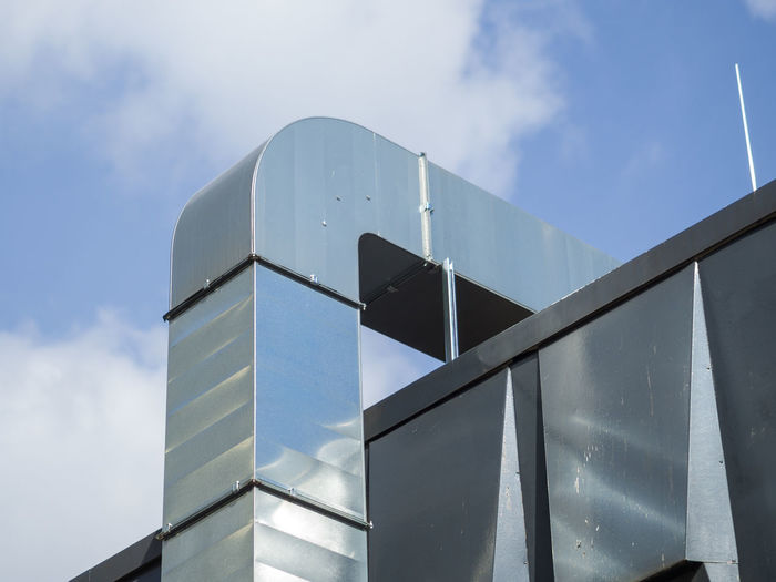 Close-Up Of Metal Air Duct On Exterior Of Building Against Sky