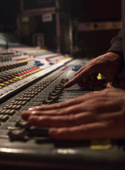 Cropped hands of dj using sound mixer
