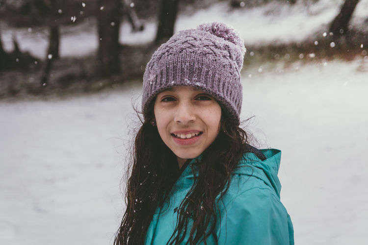 Portrait of smiling girl standing in snow
