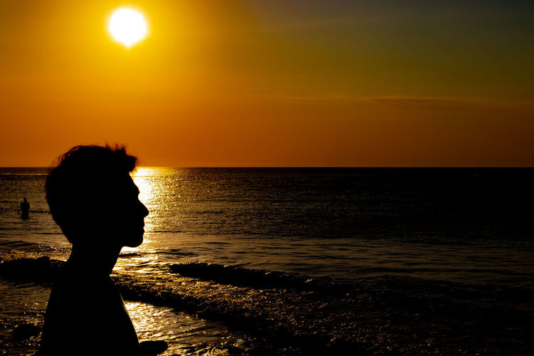 Silhouette man at sea against sky during sunset