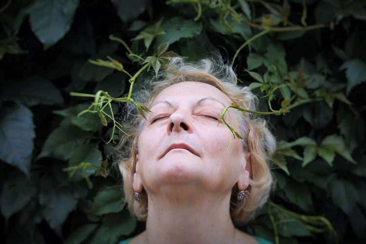Close-Up Of Senior Woman Standing With Closed Eyes By Plants