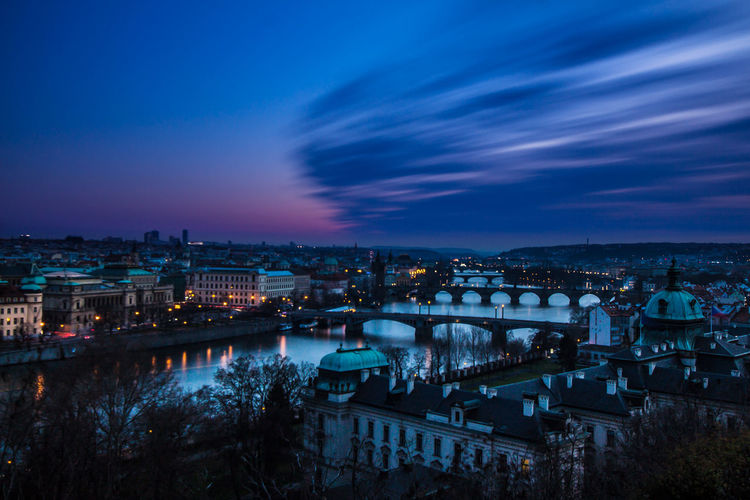 Charles Bridge Over Vltava River Against Sky In City At Dusk