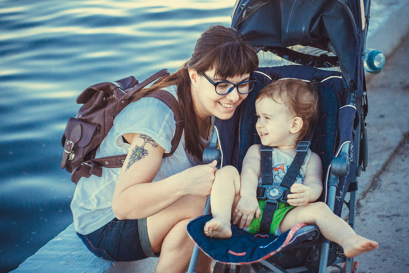 Smiling Mother Looking At Cute Son In Baby Stroller Against Sea
