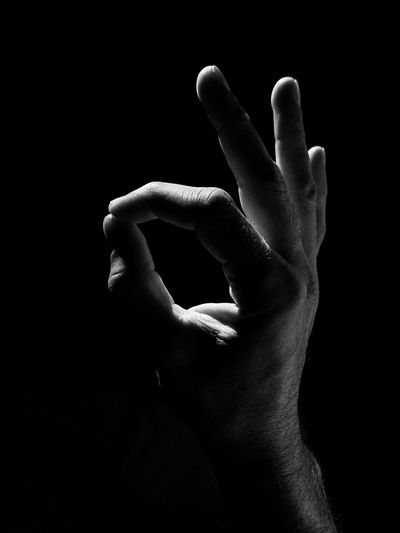 Close-up of hand over black background