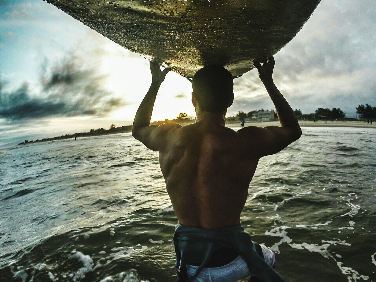 Rear view of man carrying surfboard walking towards sea
