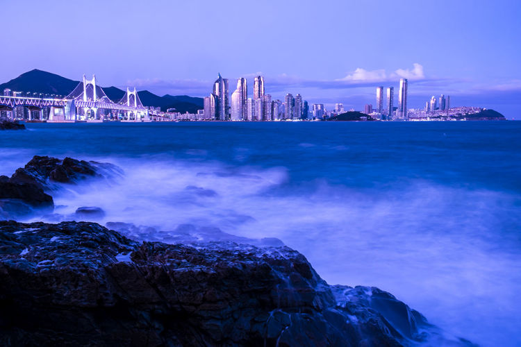 Scenic view of sea by illuminated buildings against sky
