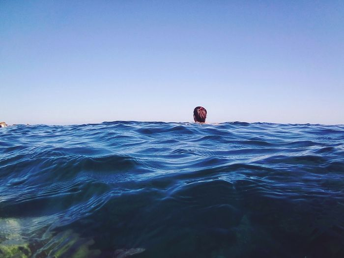 Man swimming in sea against clear sky