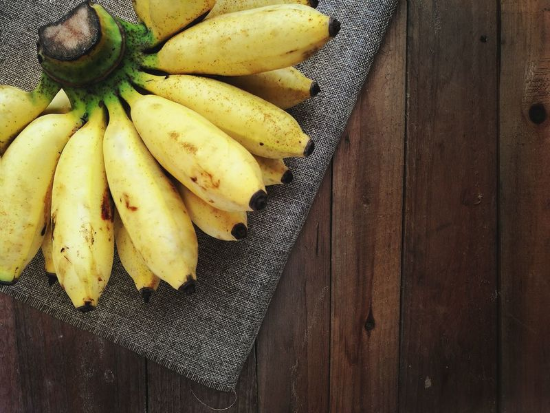 Bananas on the wooden table Food And Drink Healthy Eating Freshness Fruit Food Indoors  Table High Angle View Raw Food No People Wood - Material Day Close-up Isolated Yellow Background Texture Nature Backgrounds Copyspace Directly Above Flatlay Banana Fruit Healthyfood Nutrition Diet
