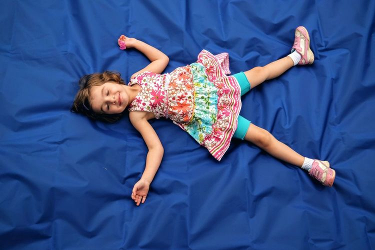 Full Length Of Cute Girl Sleeping On Blue Fabric In Yard