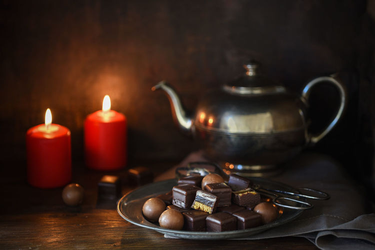 christmas chocolate sweets, two red candles and a silver teapott on a rustic wooden table, dark moody background Christmas Advent Cookies Chocolate Sweets Teapot Tea Time Break Dark Snack Copy Space Food And Drink Food Still Life No People Indoors  Candle Flame Burning Red Color Heat - Temperature Illuminated Hot Drink Rustic