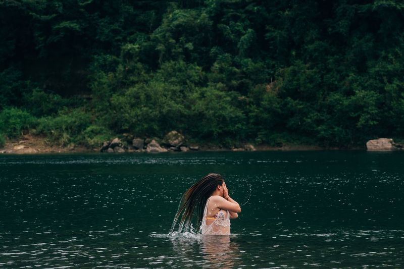 Woman tossing hair in lake